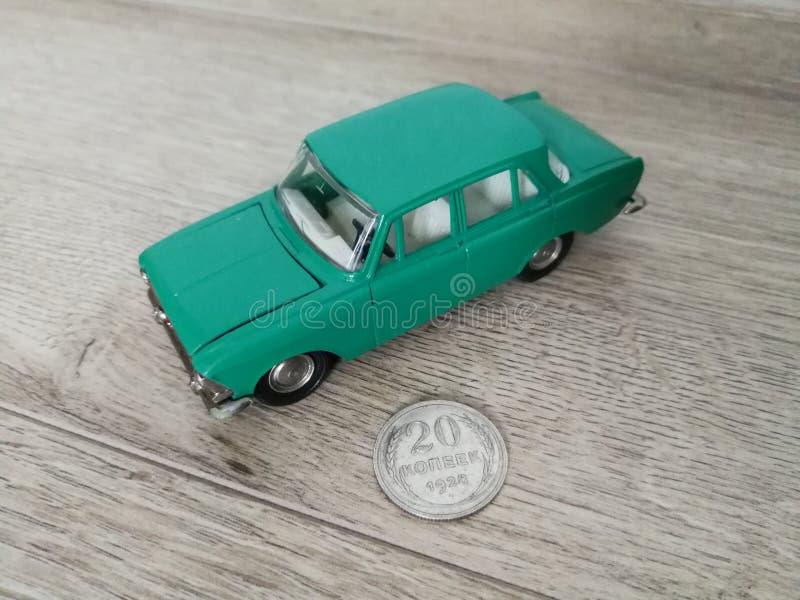 Giocattolo di modello dell'automobile in confronto alla vecchia moneta immagini stock