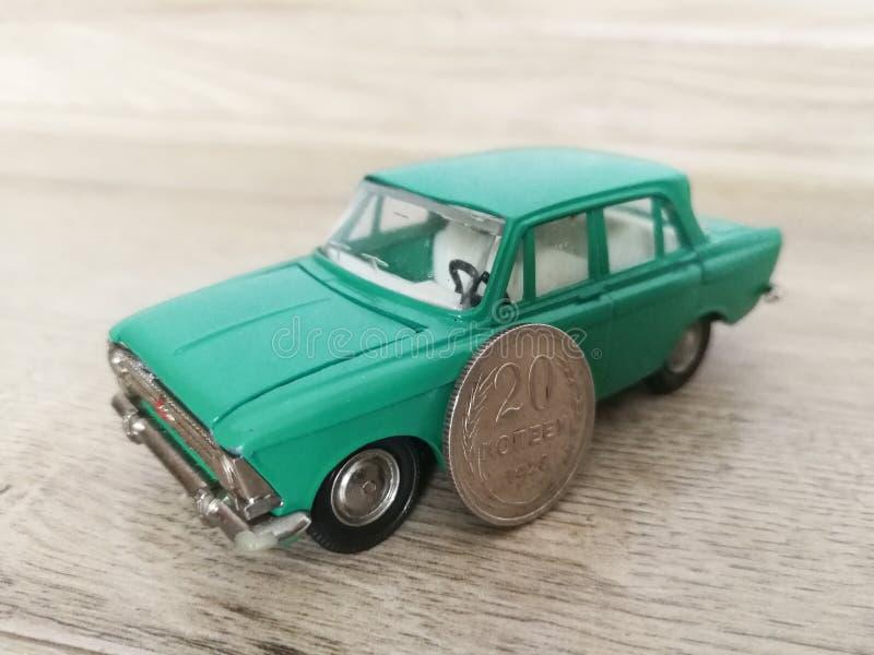 Giocattolo di modello dell'automobile in confronto alla vecchia moneta fotografie stock