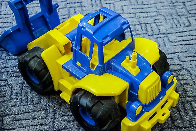 Giocattolo di plastica del trattore dei piccoli bambini blu immagini stock