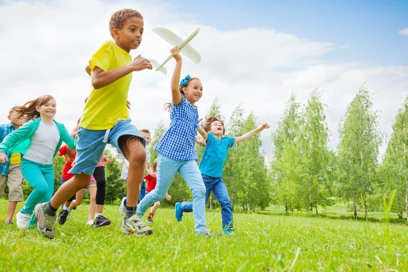Giocattolo e bambini felici dell'aeroplano della tenuta della ragazza vicino immagine stock