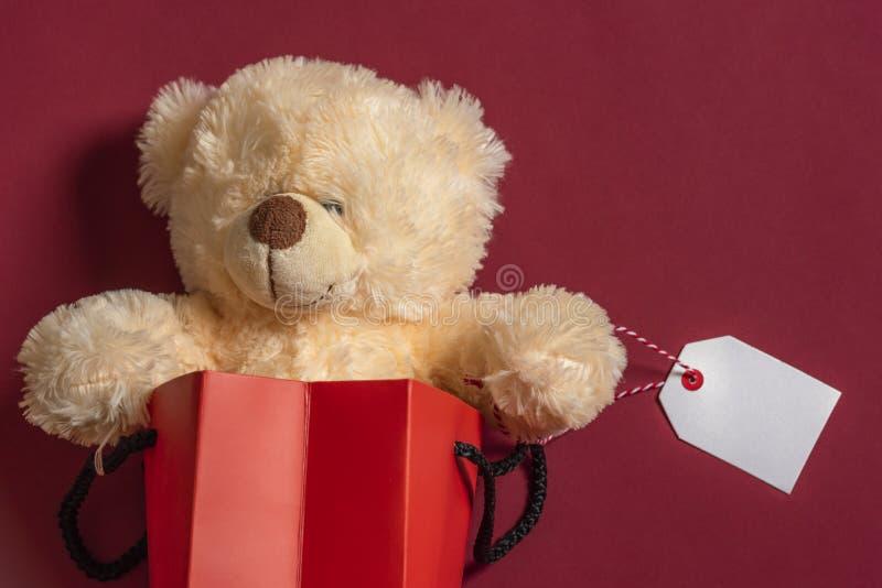 Giocattolo farcito dell'orsacchiotto in un sacchetto della spesa con l'etichetta in bianco Spazio rosso della copia e del fondo fotografie stock