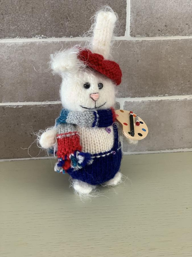Giocattolo fatto a mano sveglio dell'artista del coniglio o della lepre tricottato con le pitture e la sciarpa immagini stock libere da diritti