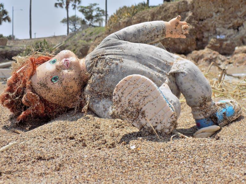 Giocattolo rotto che sta trovandosi sulla sabbia fotografia stock