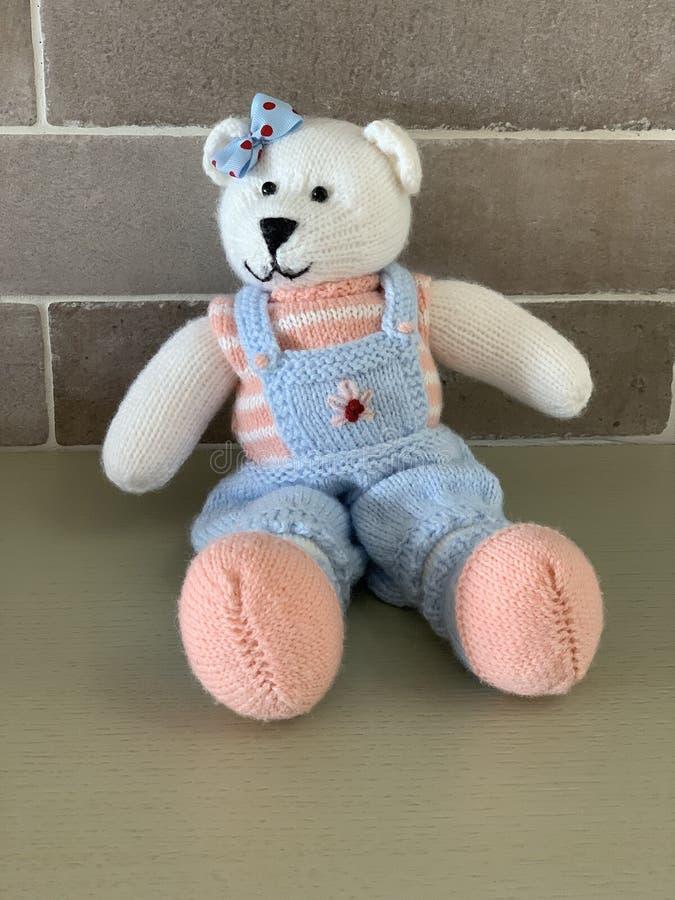 Giocattolo sveglio tricottato dell'orsacchiotto nel costume che si siede sulla tavola immagini stock libere da diritti