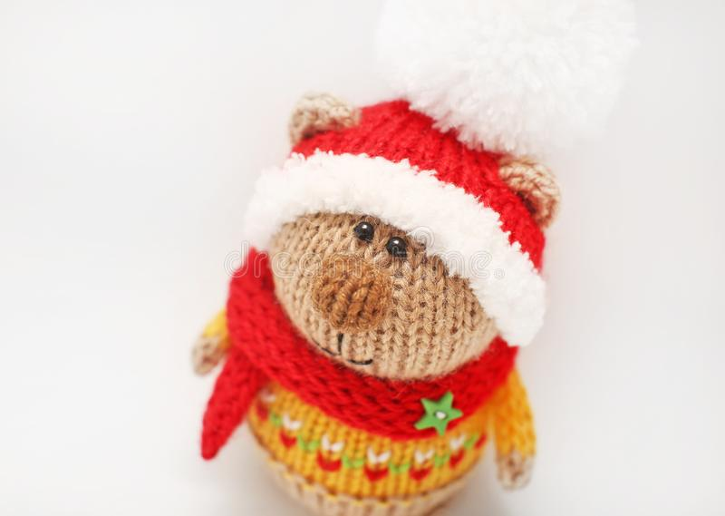 Giocattolo tricottato fatto a mano Primo piano tricottato dell'orso a colori il maglione e cappello rosso con il pompon bianco su fotografie stock