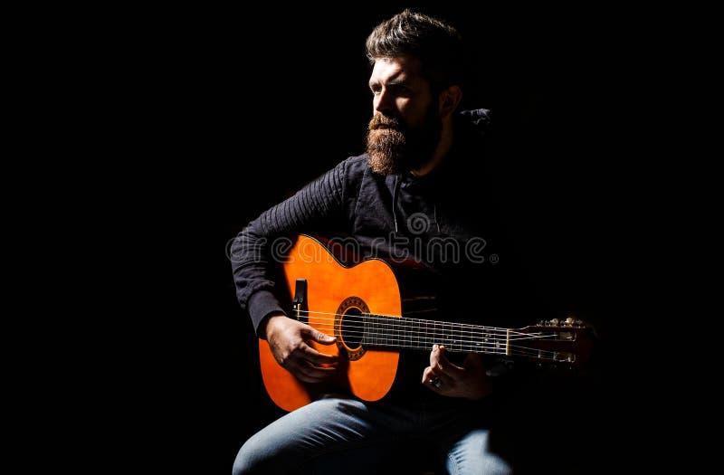 Giochi barbuti del chitarrista Giochi la chitarra Uomo dei pantaloni a vita bassa della barba che si siede in un pub Musica in di immagini stock libere da diritti