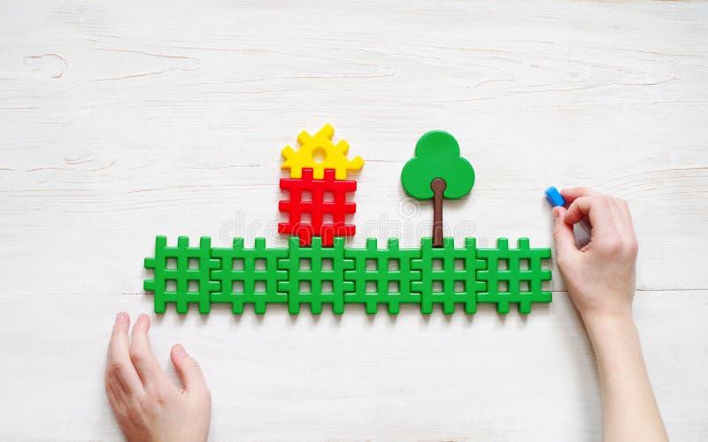 Giochi da bambini con il progettista di plastica Mani del bambino e dell'immagine della casa e degli alberi fotografia stock libera da diritti