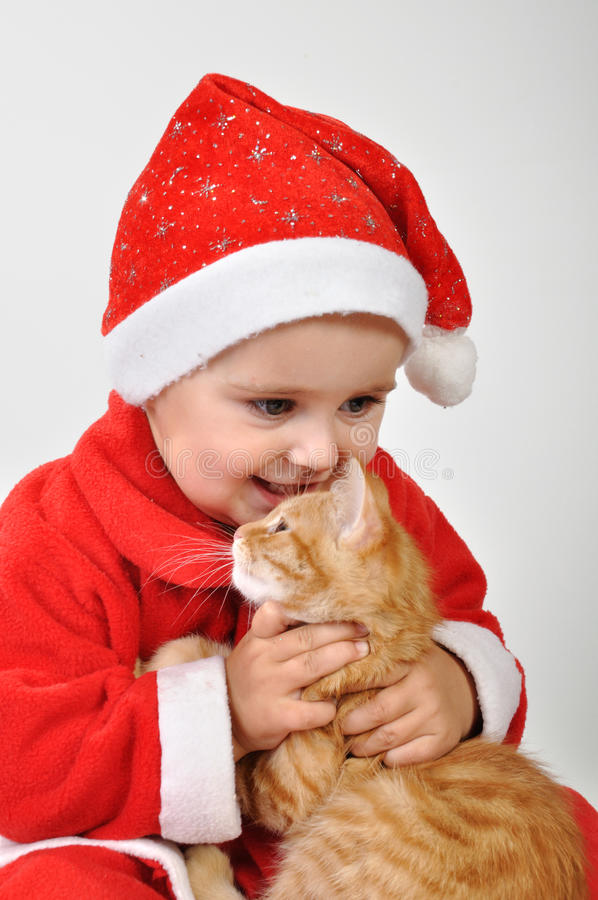 Giochi da bambini del bambino di Natale con un gatto immagini stock libere da diritti