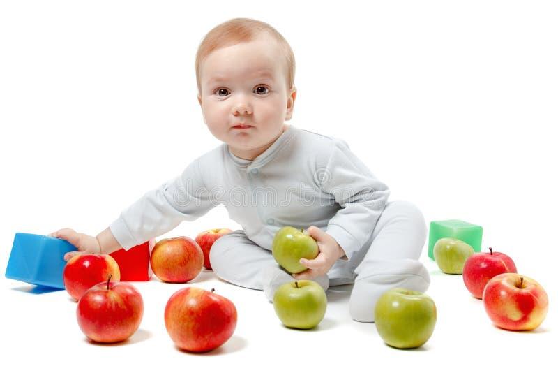 Giochi del bambino con le mele ed i giocattoli Ritratto dello studio, isolato su un fondo bianco fotografia stock libera da diritti