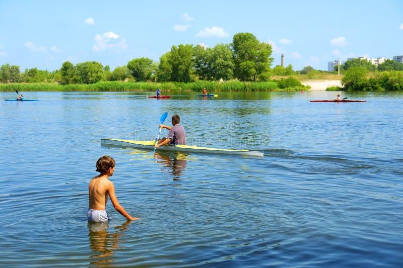 Giochi del ragazzo in acqua e barca immagini stock