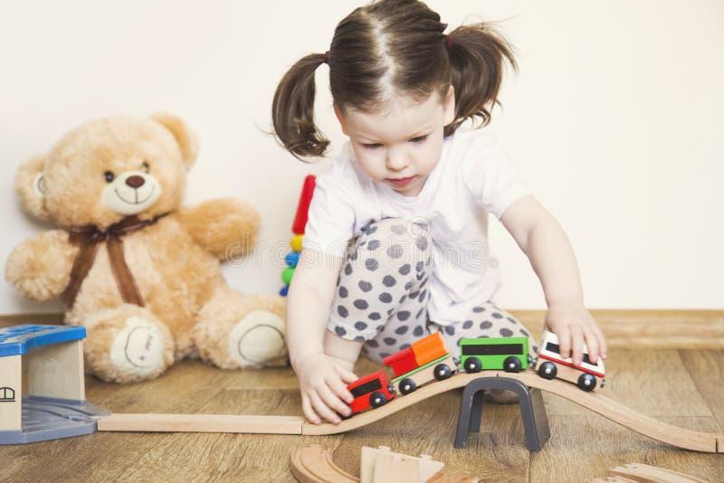Giochi della bambina con i giocattoli, la ferrovia di legno ed il treno immagini stock libere da diritti