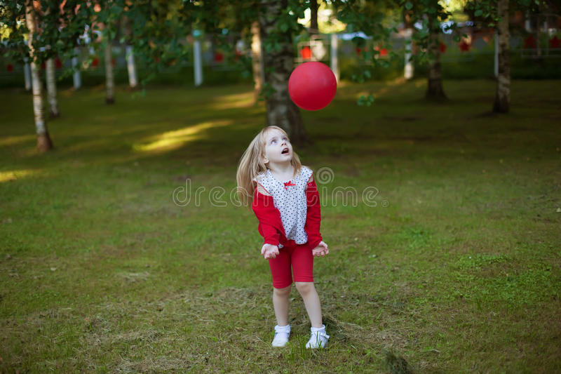 Giochi della bambina con la palla rossa fotografie stock