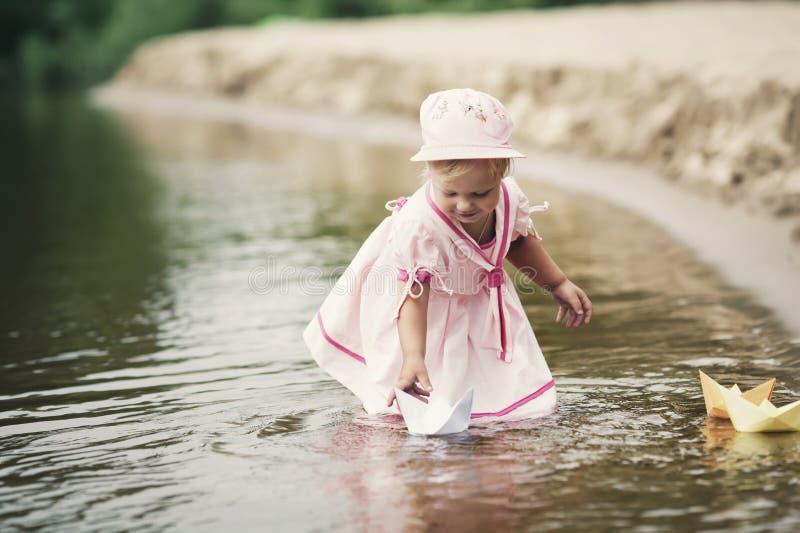 Giochi della bambina con le barche di carta fotografie stock