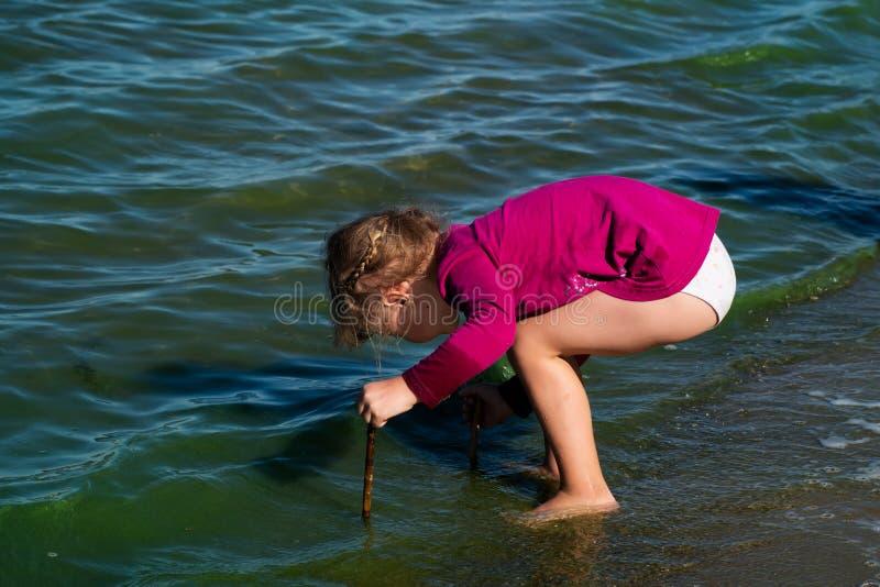 Giochi della bambina nelle onde costiere immagine stock libera da diritti