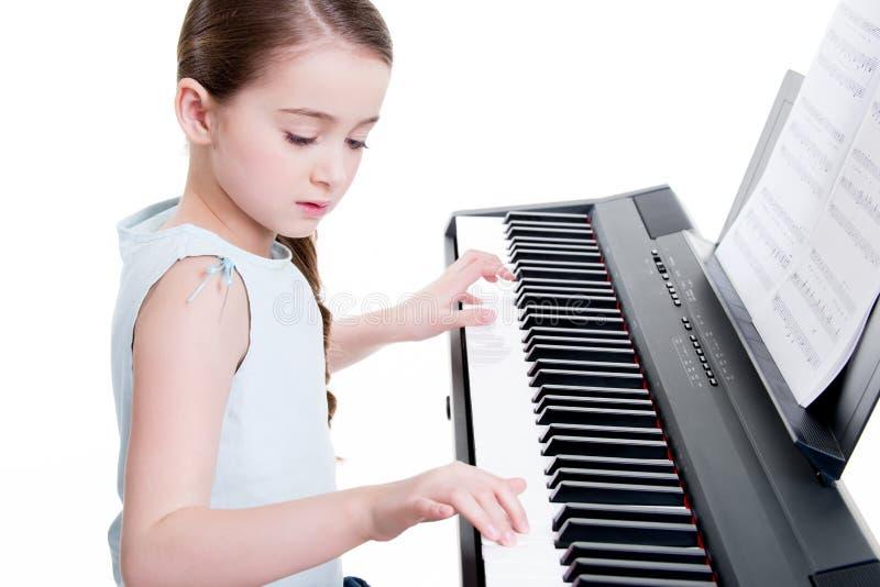 Giochi della bambina sul piano elettrico. immagini stock libere da diritti