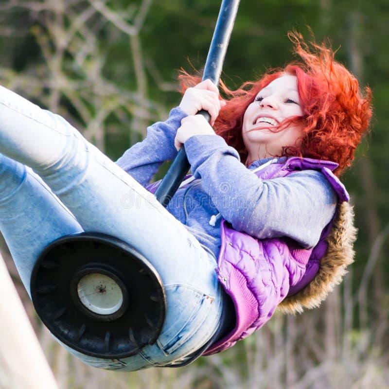 Giochi della ragazza al campo da giuoco con i capelli di volo fotografia stock libera da diritti