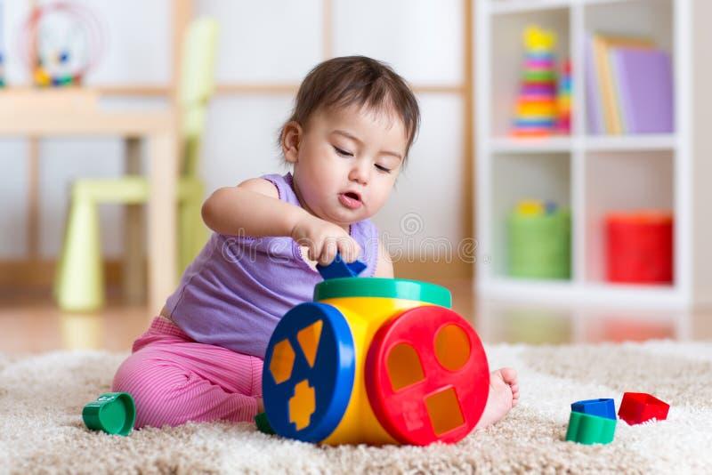 Giochi della ragazza del bambino con il giocattolo educativo dell'interno fotografia stock