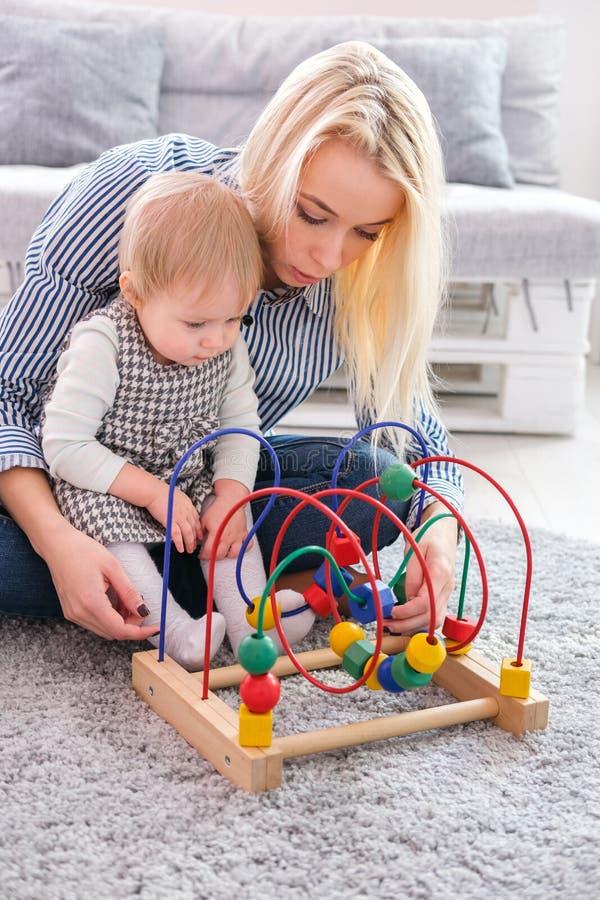 Giochi della ragazza del bambino con il giocattolo educativo dell'interno Madre felice che esamina sua figlia astuta immagine stock