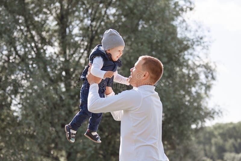 Giochi di amore del padre con il suo giovane figlio nel parco della città immagini stock libere da diritti