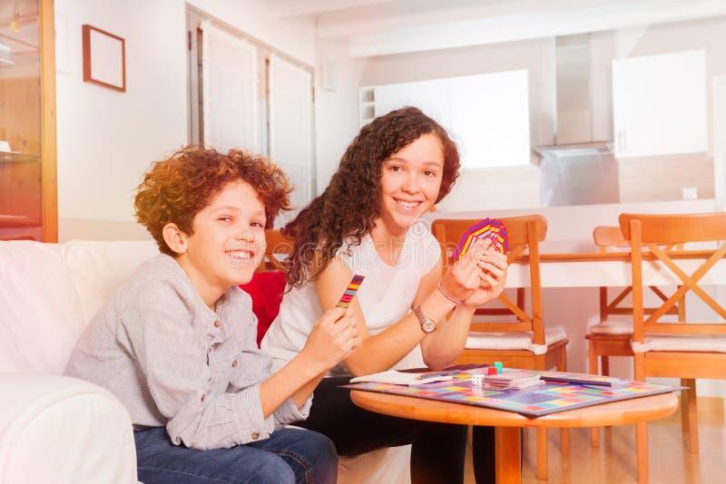 Giochi di carta da gioco felici di anni dell'adolescenza nel salone immagine stock libera da diritti