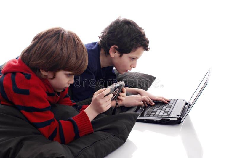 giochi di computer dei bambini che giocano video fotografia stock
