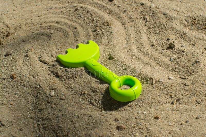 Giochi di estate nella sabbiera con i rastrelli verdi fotografie stock libere da diritti