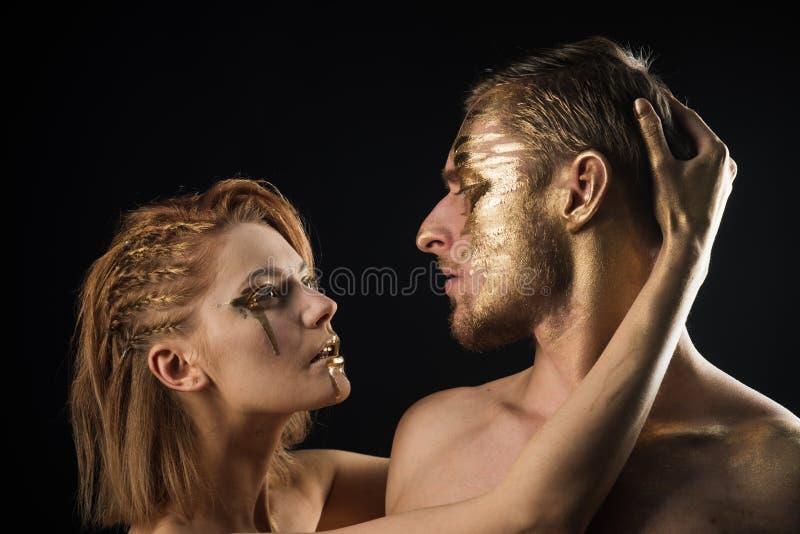 Giochi erotici delle coppie nell'amore Coppie sexy con trucco dorato di body art isolate sul nero Maschera dorata del collagene e fotografie stock