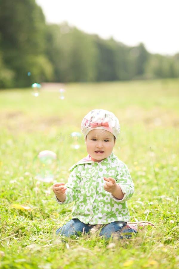Giochi graziosi della bambina con le bolle di sapone all'aperto immagine stock libera da diritti