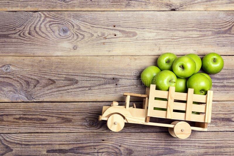 Giochi il camion di legno con le mele verdi nella parte posteriore su backgr di legno fotografia stock