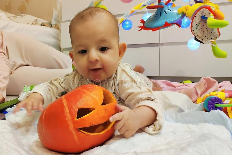 Giochi infantili della neonata con la zucca di Halloween, trovantesi vicino alla madre fotografia stock libera da diritti