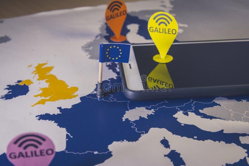 Giochi l'automobile, il perno di Galileo e uno smartphone sopra una mappa di UE Metafora del sistema di Galileo fotografie stock