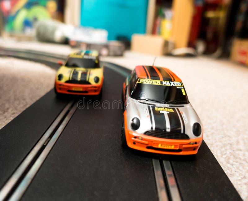 Giochi le automobili di scanalatura su una pista in una camera da letto del ` s del bambino immagine stock