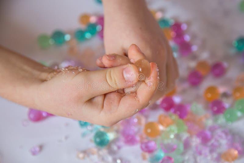 Giochi sensoriali con le perle rotte dell'acqua dell'idrogel immagine stock libera da diritti