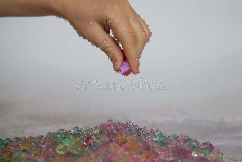 Giochi sensoriali con le perle rotte dell'acqua dell'idrogel immagine stock
