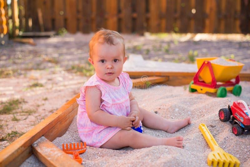 Gioco adorabile con la sabbia in sabbiera sul campo da giuoco, infanzia del bambino di estate immagini stock libere da diritti