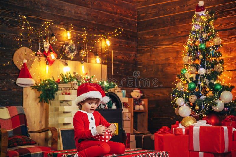 Gioco allegro di umore del bambino sveglio del ragazzo vicino all'albero di Natale Festa della famiglia Buon Natale e luminoso Il immagine stock