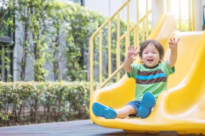 Gioco asiatico del bambino del primo piano un cursore ai precedenti del campo da giuoco fotografie stock