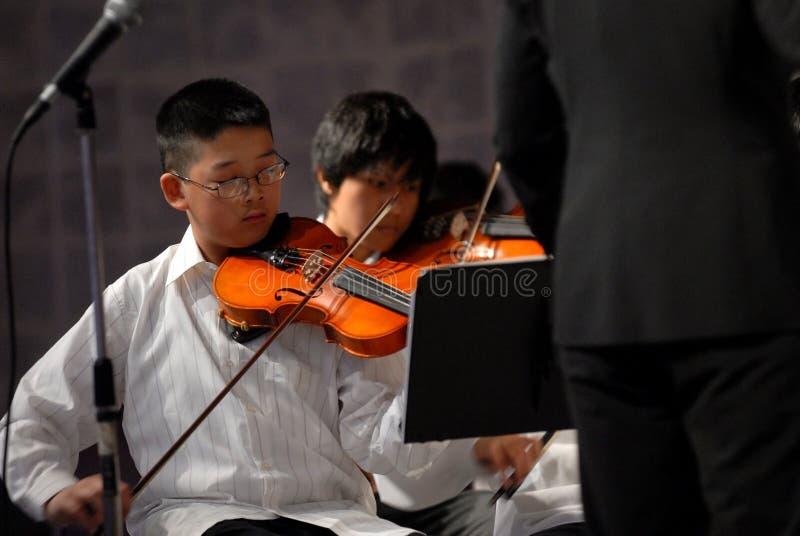 Gioco asiatico del ragazzo il violino immagini stock