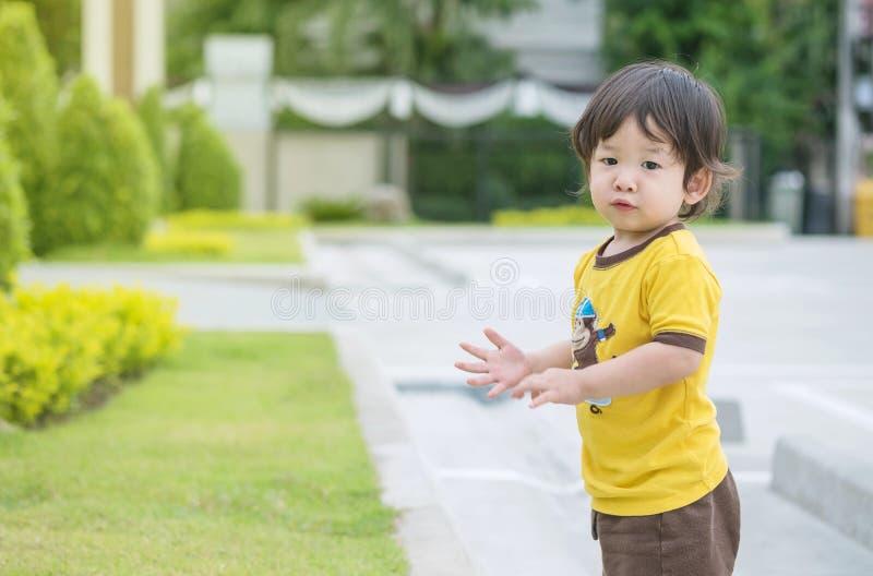 Gioco asiatico impertinente del bambino del primo piano nei precedenti del parco pubblico con lo spazio della copia fotografie stock