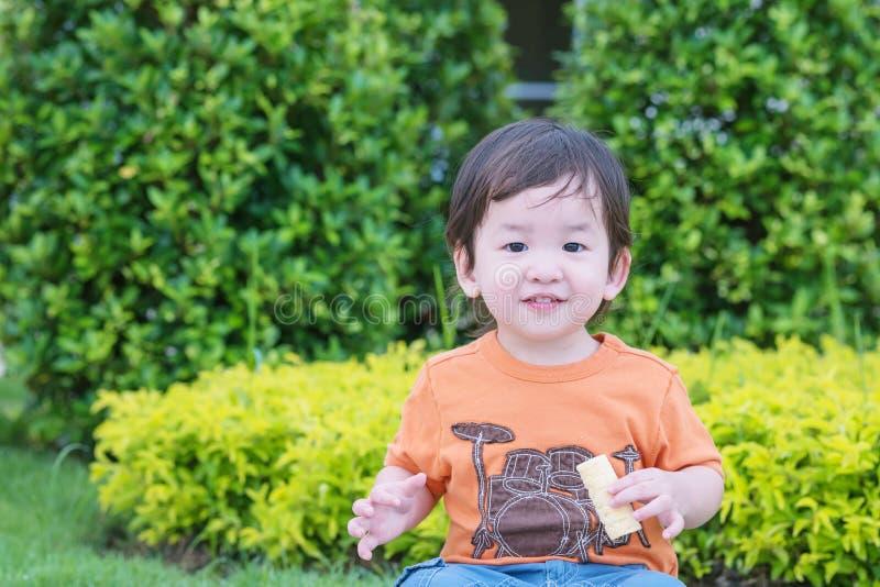 Gioco asiatico sveglio del bambino del primo piano nei precedenti del parco fotografie stock