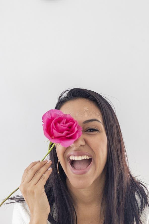 Gioco castana sorridente sveglio con una rosa fotografia stock libera da diritti