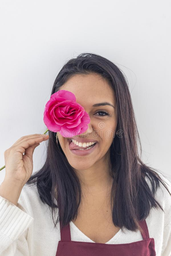 Gioco castana sorridente sveglio con una rosa immagine stock