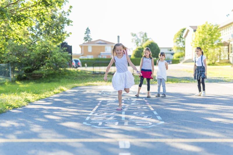 Gioco da bambini allegro di età scolare sulla scuola del campo da giuoco fotografia stock libera da diritti