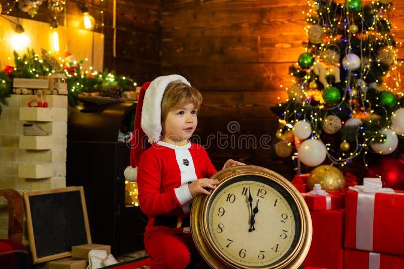Gioco da bambini del ragazzo vicino all'albero di Natale Conto alla rovescia di nuovo anno Buon Natale e luminoso Bambino adorabi fotografie stock