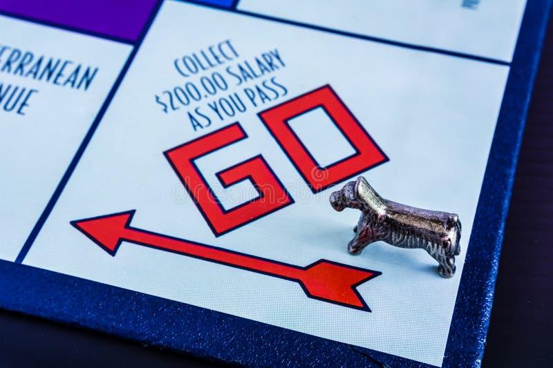 Gioco da tavolo di monopolio - il passaggio simbolico del cane VA scatola fotografia stock libera da diritti