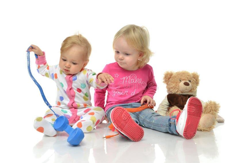 Gioco dei bambini a casa Bambini che giocano con il havi della bambina dei telefoni fotografia stock