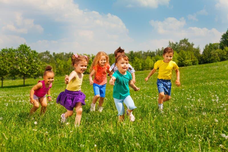 Gioco dei bambini nel campo verde durante l'estate fotografia stock