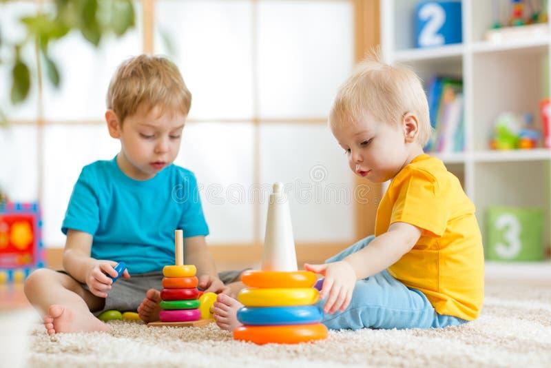 Gioco dei fratelli dei bambini insieme in scuola materna fotografia stock