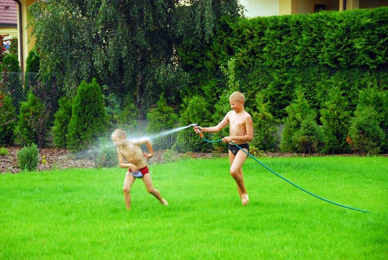 Gioco dei ragazzi sull'erba immagini stock libere da diritti