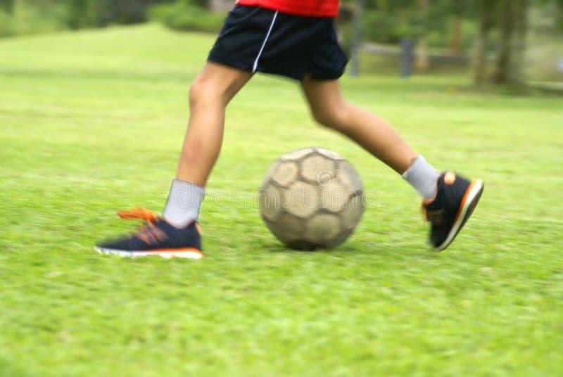 Gioco del calcio di respinta del ragazzo fotografia stock libera da diritti